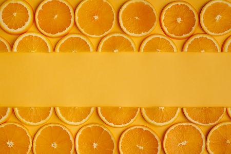 Orange slices on orange paper background.