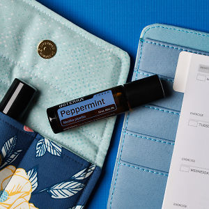 doTERRA Peppermint Touch on an essential oil bag with a diary on a blue textured background.