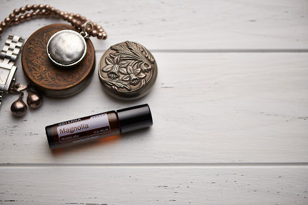 doTERRA Magnolia Touch, jewellery and trinkets on white rustic wooden background.