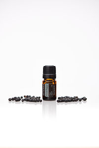 doTERRA Black Pepper with black peppercorns on a white background with reflection.