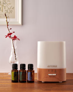 doTERRA Lumo diffuser with Cedarwood, Cypress and Siberian Fir essential oils on a side table.