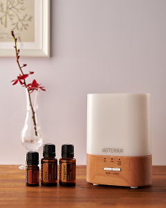 doTERRA Lumo diffuser with Cinnamon, Clove and Tangerine essential oils on a side table.