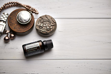 doTERRA Yarrow Pom, jewellery and trinkets on white rustic wooden background.