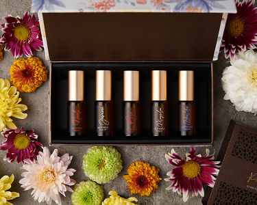 doTERRA Precious Florals Collection with scattered flowers on a gray stone background.