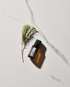 doTERRA Purify essential oil blend and a plant stem in direct sunlight on a white marble background.