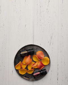 doTERRA Passion and Sandalwood with yellow and pink rose petals in a grey ceramic plate on a white wooden background.