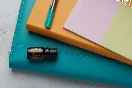doTERRA Clementine oil with business folder, planner, pen and to do list on white concrete background.
