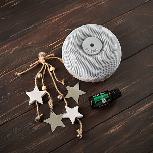 doTERRA Brevi Stone Diffuser and Holiday Peace with holiday decorations on a brown wooden background.