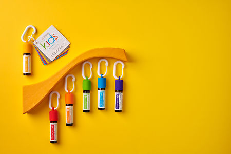 doTERRA Kids Oil Collection  oils with caps and carabiners and flashcards, featuring Thinker, on a yellow paper background.