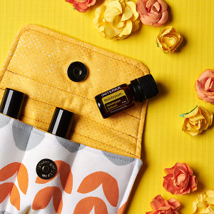 doTERRA Helichrysum on an essential oil bag with scattered flowers on a yellow textured background.