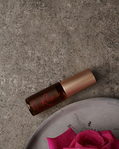 doTERRA Rose Touch 4ml with flowers on a gray stone background.