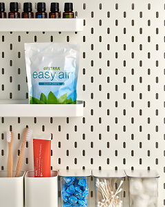 doTERRA Easy Air Clear Drops on a bathroom shelf with bathroom accessories and additional doTERRA products.
