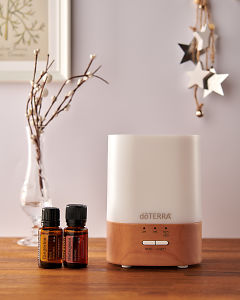 doTERRA Lumo diffuser with Tangerine and Wintergreen essential oils and holiday decorations on a side table.