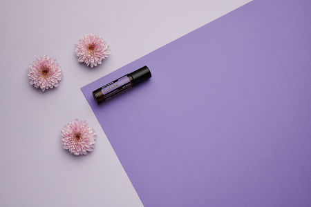 doTERRA Console Touch with pink flowers on a dark and light purple background.