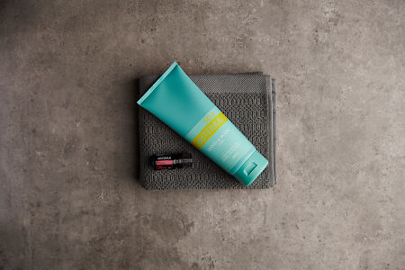 doTERRA Spa Hand and Body Lotion with Rose essential oil on a stone background.