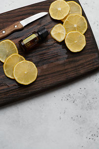 doTERRA Lemon oil, lemon slices and knife on rustic wooden chopping board with white concrete background.
