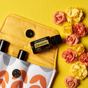 doTERRA Elevation on an essential oil bag with scattered flowers on a yellow textured background.