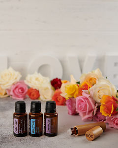 doTERRA Patchouli, Ylang Ylang and Lavender with a bamboo roller bottle and roses on a concrete bench top.