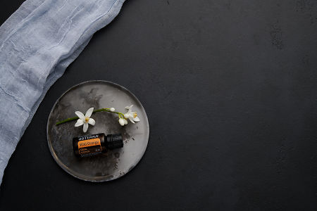 doTERRA Wild Orange with orange blossom flowers on a ceramic plate on a black concrete baclground.