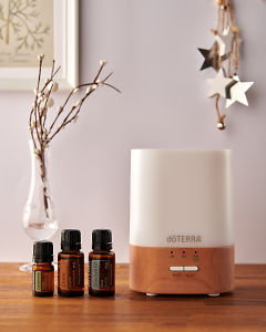 doTERRA Lumo diffuser with Cardamom, Clove and Siberian Fir essential oils and holiday decorations on a side table.