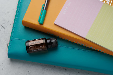 doTERRA Grapefruit oil with business folder, planner, pen and to do list on white concrete background.