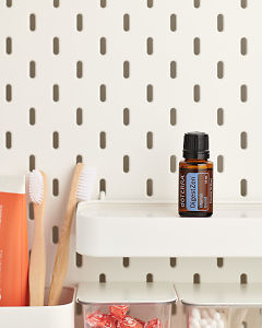 doTERRA DigestZen Internal Blend on a bathroom shelf with additional doTERRA products and bathroom accessories.