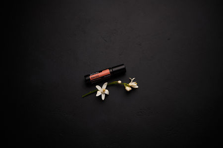 doTERRA Neroli Touch with orange blossoms on a black concrete background.