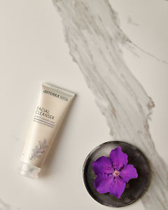 doTERRA Facial Cleanser with a purple flower in a gray ceramic plate on a white marble background.