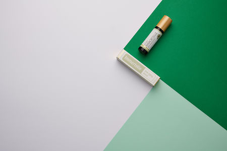 doTERRA Immortelle and product box on dark green, light green and white geometric background.