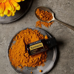 doTERRA Turmeric essential oil and ground turmeric on a ceramic plate, a yellow flower on a ceramic plate and turmeric in a teaspoon on a grey stone background.