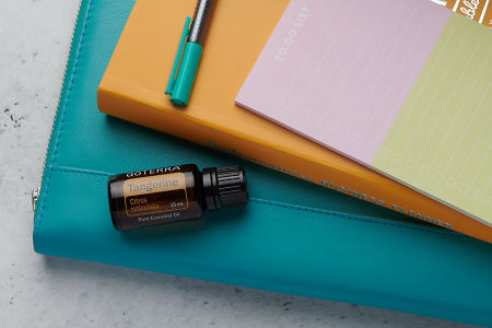 doTERRA Tangerine oil with business folder, planner, pen and to do list on white concrete background.