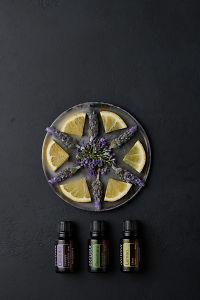 doTERRA Rosemary, Lavender and Lemon with  rosemary flowers, lavender flowers and lemon slices on a ceramic plate on a black concrete background.