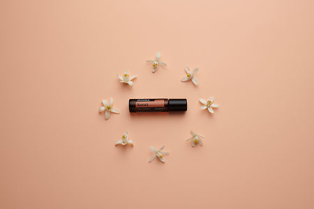 doTERRA Neroli Touch circled by orange blossoms on a pale salmon orange background.