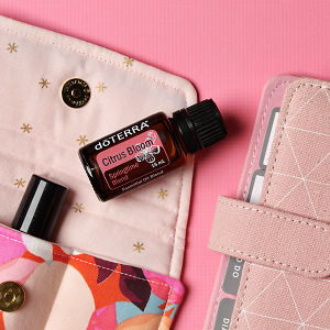 doTERRA Citrus Bloom on an essential oil bag with a pink diary on a pink textured background.