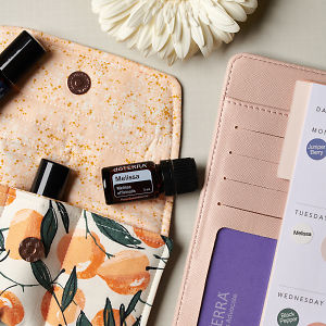 doTERRA Melissa on an essential oil bag with a white flower and diary on a white textured background.