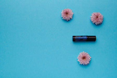 doTERRA Deep Blue Touch with pink flowers on a blue card stock background.