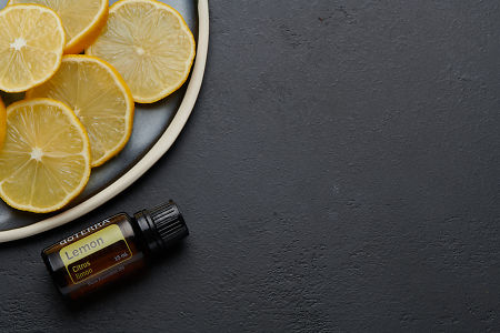 doTERRA Lemon oil and lemon slices on blue ceramic plate with black concrete background.