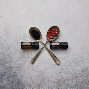 doTERRA Black Pepper and Pink Pepper with black and pink peppercorns in vintage spoons on a white concrete background.