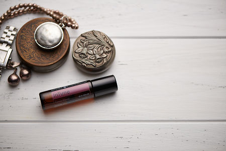 doTERRA InTune blend, jewellery and trinkets on white rustic wooden background.