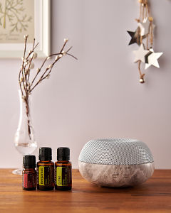 doTERRA Brevi Stone diffuser with Passion, Bergamot and Lime essential oils and holiday decorations on a side table.