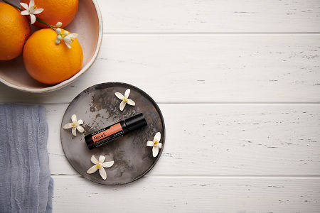 doTERRA Neroli Touch with orange blossom flowers on a ceramic plate with a white ceramic bowl filled with seville oranges and orange blossoms on a white wooden background.