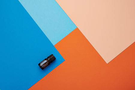 doTERRA Whisper on a blue and orange geometric background.