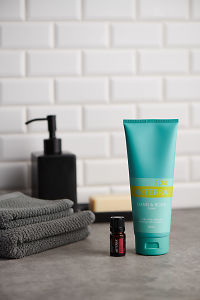doTERRA Spa Hand and Body Lotion and Rose essential oil with bathroom accessories on stone bench