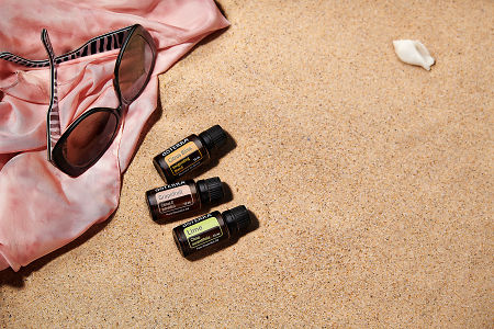 doTERRA Citrus Bliss, Grapefruit and Lime with sunglasses and a pink silk scarf on the beach.