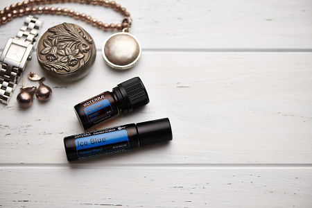 doTERRA Ice Blue oil and Ice Blue Roll On, jewellery and trinkets on white rustic wooden background.