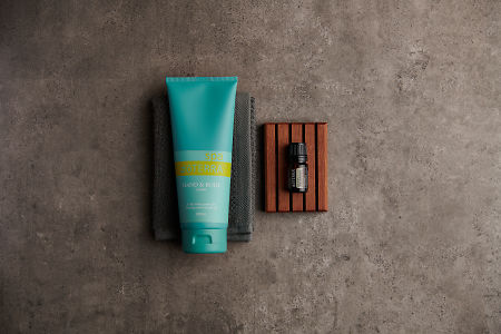doTERRA Spa Hand and Body Lotion with Hawaiian Sandalwood essential with bathroom accessories on a stone background.