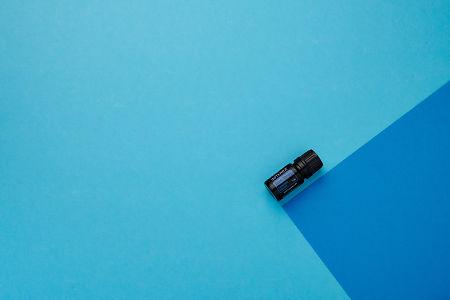 doTERRA Blue Tansy on a dark blue and light blue geometric background.
