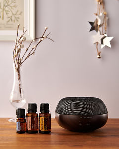 doTERRA Brevi Walnut diffuser with Juniper Berry, Grapefruit and Wild Orange essential oils and holiday decorations on a side table.