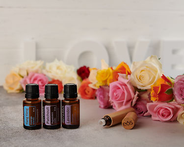 doTERRA Ylang Ylang, Patchouli and Lavender with a bamboo roller bottle and roses on a concrete bench top.