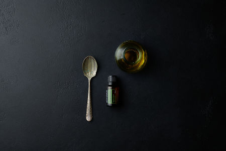 doTERRA Rosemary with a vintage spoon and a jar on a black stone background.